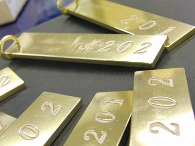 四国地方の小豆島にてペンションを経営されているお客様より、手作りの真鍮削り出し+部屋番号を1つずつ手彫りにて彫刻したルームキーのご依頼を頂きました。      全ての部屋番号が違うということから、金型や、成形にて、ある程度の単位での一括の製作は難しく、どうしても職人の手作業を随所に入れ込みながらの製作となりました。