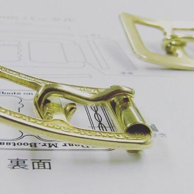 お客様オリジナルのブーツや革靴に使用させる、真鍮製のロゴ入りローラーバックルのオーダー。