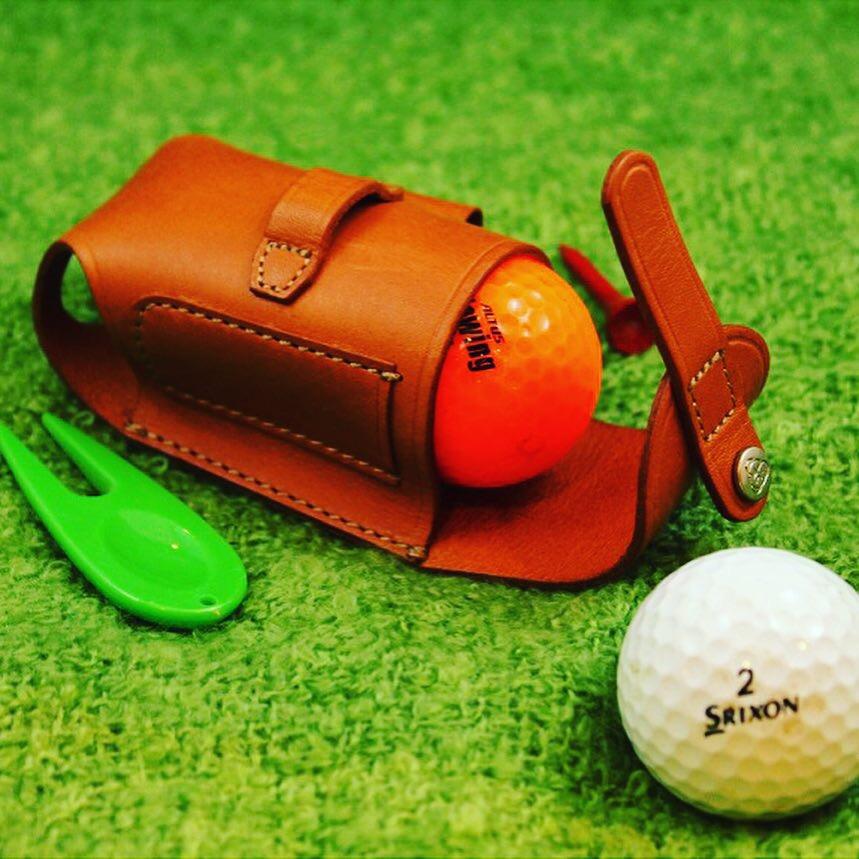オリジナルゴルフボールケース、ベルト、キーホルダーの特注オーダー。 ・  1. ゴルフボールx2個+ティーx2本+デポット直しx1個をベルトループに取り付けて、ラウンドできる革小物。 ・ 2. オリジナルのデザインから製作したバックルを取り付けた、オーダーメイドのベルト。 ・ 3. 特注のロゴ入りのカシメを使用した、オリジナルのキーホルダーの製作。