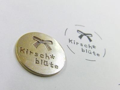リールキー(携帯電話や、ID、パスなどに取り付け、長さが伸び縮みする優れものの金具)に取り付けるオリジナルのロゴ、ネーム入り金具のご注文を頂きました。