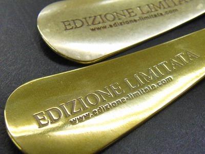 """お客様オリジナルブランドのロゴを刻印した、真鍮製、オーダーメイドの靴べらキーホルダーの製作。真鍮は加工がしやすく、またアジ""""経年変化""""を楽しむことの出来る馴染みのある素材です。まるで生きているかの様に、1日1日飴色に表情を変化させていきます。金型から打ち抜かれた製作直後の真鍮を丁寧に磨き上げ、手触りの良さを際立たせてから、真鍮地金の素顔の状態での納品。"""