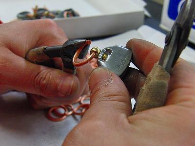 手作業にてキーホルダーになる、フックのパーツを取り付け