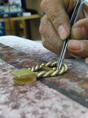 ひねり金具の本体となる部分と、縄目模様の線との位置を正確に決めて、ロー付け(純銀を使用した、強度があり、綺麗に溶接できる方法)していきます。