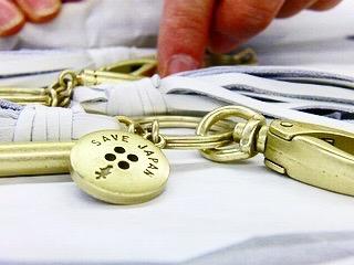 アパレルブランドさまが、Save Japanを合言葉に、災害の際に実際に使用可能な笛を付属した、ファッション性のある社会貢献的要素を盛り込んだオリジナルのキーホルダー