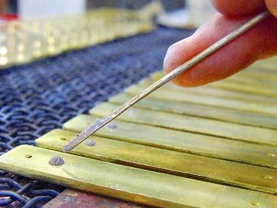 グレーの液体に800cの熱を加えると、純銀が溶け出し、真ちゅう製の足とプレートを溶接していきます。