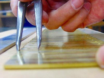バッグに取り付けるネームプレートの為に、裏面に割り足をロー付け(純銀を使用した強度のある溶接)します。