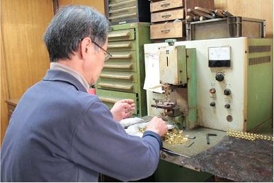 挽いて切られた金属。型抜きされた金属。      他の職人から届けられた小さな金属がまた別の職人の技によって一つの形に。  多いときは1,000ヶ、5,000ヶものロー付けを行います。      ひとつひとつ丁寧に手作業にてロー付けされた部品は、とても美しいものです。