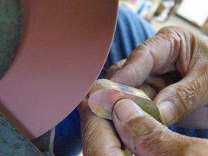 """ひねる部分の機械的な構造を取り付けるために""""縦フライス""""という機械にて金具に溝を掘っています。 次にグラインダー(金属を荒削りする機械)にて正面や、側面に均一感を持たせていきます。"""