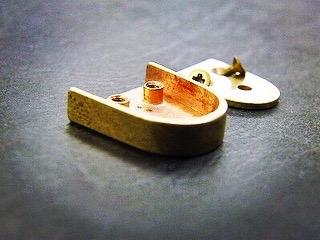 一見普通の金具に見えるのですが、裏面に特殊なホックを取り付け、また、この金具を2つ1組で使用することで、特許取得をされています。
