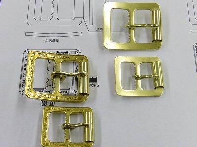 ブーツのバックルとして使用される為に、ピンを取り付け、弊社の面取り、艶だし加工を施し、頂いた図面と繰り返し照らし合わせ、確認作業を続けて行きます。      大きさのチェック。