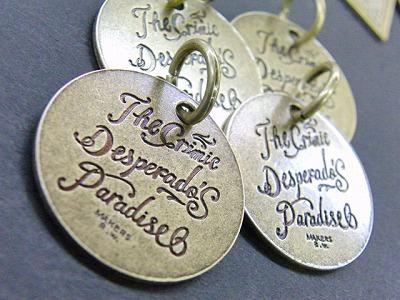 メダルネームプレートの方でも同じく、アンティークゴールド加工を施しました。    ハードな感じのブランドなので、このアンティークゴールドとの愛称は抜群に良いと思います。