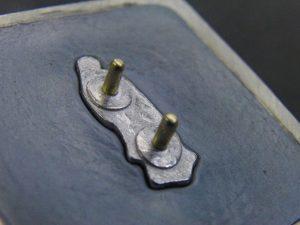 裏面に2ヶ所のホックを取り付けることで取り付けた際に、左右に動くのを防ぎ、しっかりと商品に固定することが可能になります。  今回は極小のカシメです。