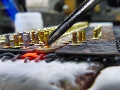 頂いたデザインを元に、金型を1型作成し、プレス機にて打ち抜いたホックです。表面のデザインは同じデザインになりますが、これから裏面に使用用途の違うパーツをロー付けし、さまざまな用途に使用可能なオリジナル金具に変化させていきます。