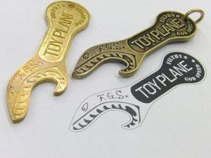 ロゴ入りのオリジナル栓抜き金具の製作依頼を頂きました。上に見えるのが、いわゆる原型 です。原型は素押し金具を同様に真ちゅうの板から、熟練の職人の技術により世界で一つだけの金具が作成されていきます。 真ちゅうの板から手作業で作り出さ れたとは思えない程の美しい出来映えの原型です。 この原型が全ての商品の出来映えを左右する程大変重要な金具になります。
