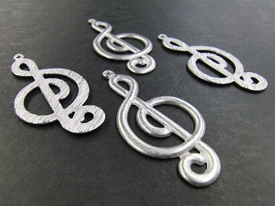 亜鉛でのキャスティングですので、真ちゅう鋳物よりも、表面につやが出たり、繊細さが表現できます。    ♪音符形のチャーム。金具一つの原型を作り出し、それを元に製品を作成します。 今回は、形状と、お客様のご要望の風合いを出すために、ラバーキャスティングの製法で作成いたしました。