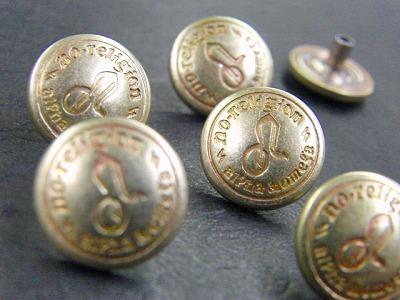 """真鍮を利用して様々な特注、オリジナルの金具をオーダーメイドで作れます。 Original Brass Fittingfs      メタルハウスで一番使用する材料が""""真ちゅう""""という材料です。     真ちゅうの特徴は、磨き上げると金の様な輝き、艶を出せたり、また時間や使用頻度により経年劣化が楽しめるという点があります。      また、メッキ加工を施す際にも、金、銀、その他の金属との相性が良く、光沢を出しやすいという利点がある優れた素材になります。    少しですが、真ちゅう製の商品をお見せいたします。      北海道のお客様から頂いた、オリジナルのロゴ入りの真ちゅう製のジャンパーホックです。"""