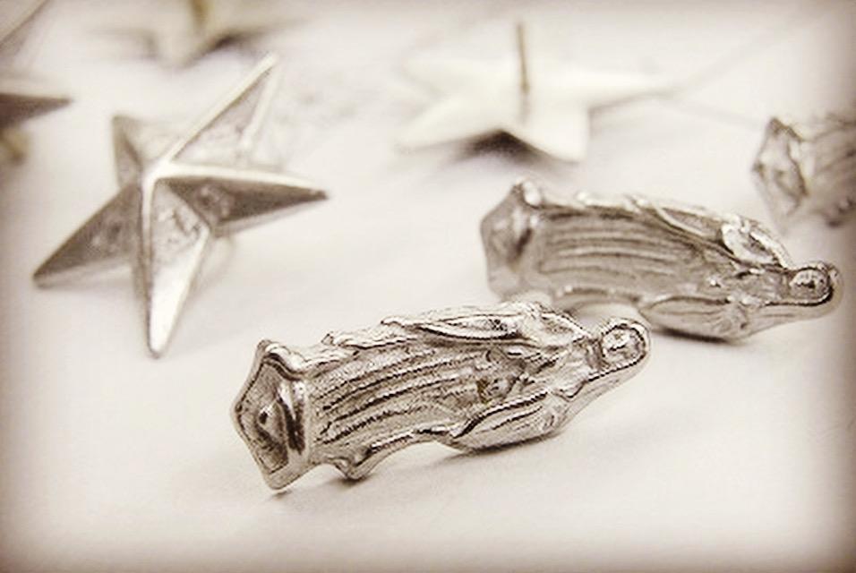 その後冷やされたスター形の金属の表情です。頂いたスターのオリジナル金具は、カシメ、カフスボタン、そしてネックレス様に加工していきます。中央に彫刻された英文字が見えますか?  ここにアルファベットを彫り込むのは、非常に熟練の職人技なんです。