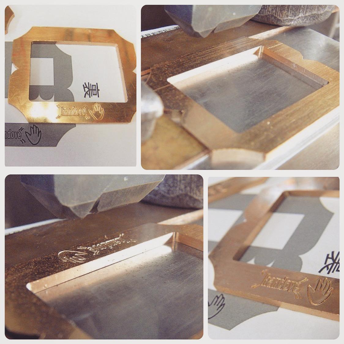 真ちゅう磨き仕上げなので、真ちゅう特有の経年変化(味)を楽しむ事ができます。  真ちゅうを彫刻機にて削り出し、成形した後に、お客様ご指定のロゴとモチーフを手作業で刻印していきます。上部に少し見えるのが鋼製(日本刀と同じ材料)の刻印になります。