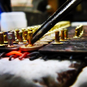 金具の表面は同じ型を使用しているので、当然同じデザインなのですが、メタルハウスの溶接の技術で、今回のように、ホックやチャーム、さまざまな用途に使用できるパーツを取り付けることで、型代を複数掛ける必要がなく、さまざまな用途にオリジナル金具を使用することが可能になります。