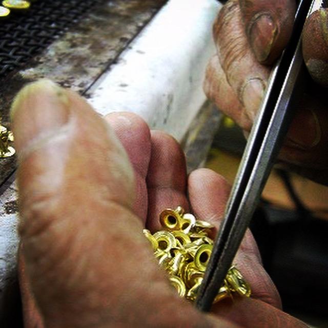今回は大カシメとチャームの金具にしたいとのご要望でしたので、まずは、裏面に手作業にて、大カシメとチャームのパーツをロー付けしていきます。(純銀を使用した強度のある溶接方法)    ホックと、大カシメとオスのパーツが熟練の職人の手によって、一つずつ溶接の下準備がされています。
