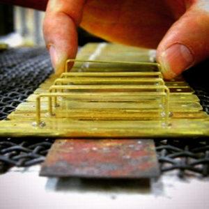 今回のお客様は光沢メッキ、最高級のクオリティーがお望みとの事でしたので、本体部分の金具と、ピラミッドの金具の部分を、別工程で、バラバラにて製作していきます。 穴が開いているのは、溶接の液体、メッキの液体が溜まらずに流れ落ちるようにしています。こうすることで、100%乾燥させたり、余計な液体が残り、品質が落ちることを防ぎます。