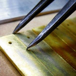 フラットなネームプレートの上に、凸形のピラミッドを取り付けて、また、光沢のあるメッキ仕上げをご希望している為に、それぞれの金具のパーツをそれぞれ別途作成し、後加工で取り付けして行く方向で製作していきます。