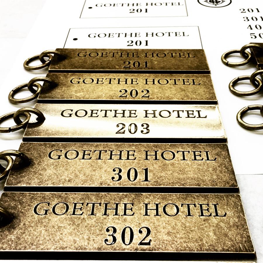 通常であれば、個別のネームやロゴ、シリアルナンバー、ホテルのルームキーなどのナンバリングを製作するのに一つ一つ職人が手彫りにて彫刻する為に高額な費用が必要になりますが、メタルハウスでは、特殊な化学技術を使用することで、真鍮板に直接個別な文字や数字、部屋番号などを、費用を可能な限り軽減しながら、お客様のイメージを金具にする事ができます。