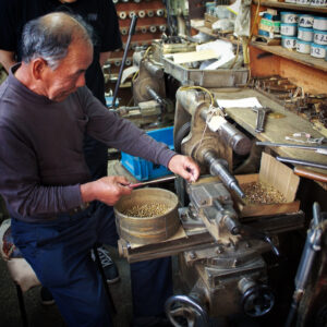 """""""挽き物職人""""金属を切断、彫刻、削り、穴あけ、ねじ切りに特化した技術。挽き物とは金属を挽いて、金具を切り出したり、金属に溝を彫ったり、作ったりする技。真鍮の板材、丸材をメインの素材として扱い、デザインや図面に合わせて形を成形していく、1920年代から続く、古くからある日本の伝統技術。"""