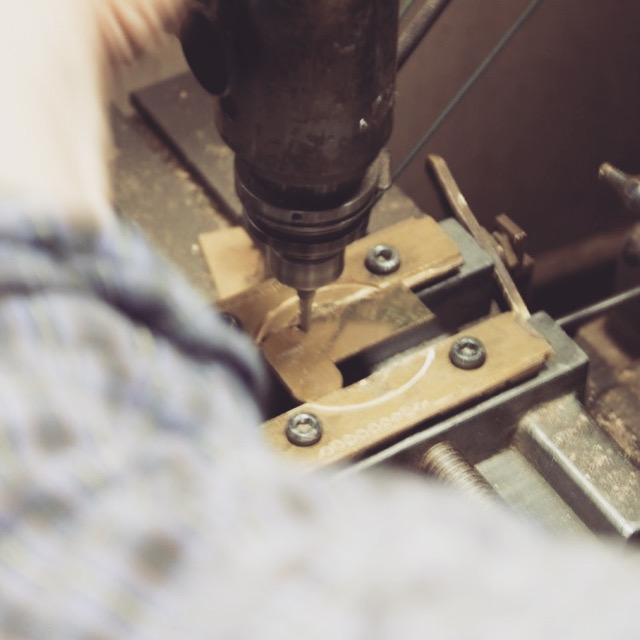 """大小各100セットの注文の為、大掛かりな型での作成ではなく、手作業にて材料を真ちゅうを板材から削り出す""""挽きもの""""という技術つを応用して、形を成形していきます。"""