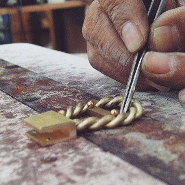 まずは、ひねり金具の本体となる部分と、縄目模様の線との位置を正確に決めて、ロー付け(純銀を使用した、強度があり、綺麗に溶接できる方法)していきます。 職人さんの手は、風格と歴史を感じられて、格好いいと思うのは僕だけでしょうか?