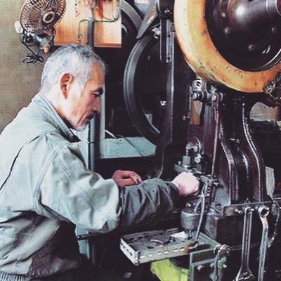 住宅街の中にある弊社のプレス職人の工場。ドアを開けるとうっすら差し込む光の中、プレスの音だけがもくもくと響いています。工場内に漂う沈黙と機械音のコントラストが、70年以上に渡って小さな金属の部品を刻んできた歴史を際立たせています。