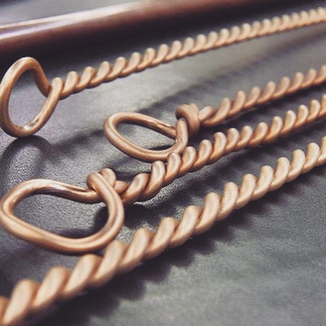 熟練の職人手作り、真鍮製バッグ用ひねり金具、オリジナル金具のオーダー Original Metal Turn Lock Fittings 東京の台東区にて爬虫類の革を中心にバッグや、小物を作成されていらっしゃる老舗のメーカーさまから、ハンドバック用の、特注ひねり金具のご依頼を頂きました。 全てのパーツを手作業にて取り揃えていきます。 ひねられている真ちゅう製の鎖のように見えるのは、2本の真ちゅう製の丸線の材料を2本束ね、それを丁寧に手作業にてねじり上げ、縄目線を作成します。 ロット数が少なくても作成できる方法で、なおかつ、大量生産では作り出せない、立体感、奥行きのある網目模様を作り出せることができます。
