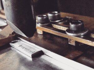 住宅街の中にある弊社のプレス職人の工場。ドアを開けるとうっすら差し込む光の中、プレスの音だけがもくもくと響いています。工場内に漂う沈黙と機械音のコントラストが、70年以上に渡って小さな金属の部品を刻んできた歴史を際立たせています。 🔨 Original engraved brand logos on your original double rings can give some impacts on your brand images.