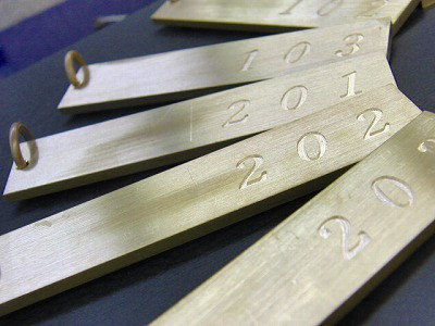 長年付き添って共に日本のモノ作りを支えてきたう彫刻機という道具。右手で部屋番号が彫刻された母型といわれる原盤をなぞっていくと、左手にあるルームキーホルダーに番号が1つずつ彫刻されていく道具。    職人の細やかな繊細な動きを、まるで生きているかの様に汲み取って、彫刻をしてくれる優れものです。